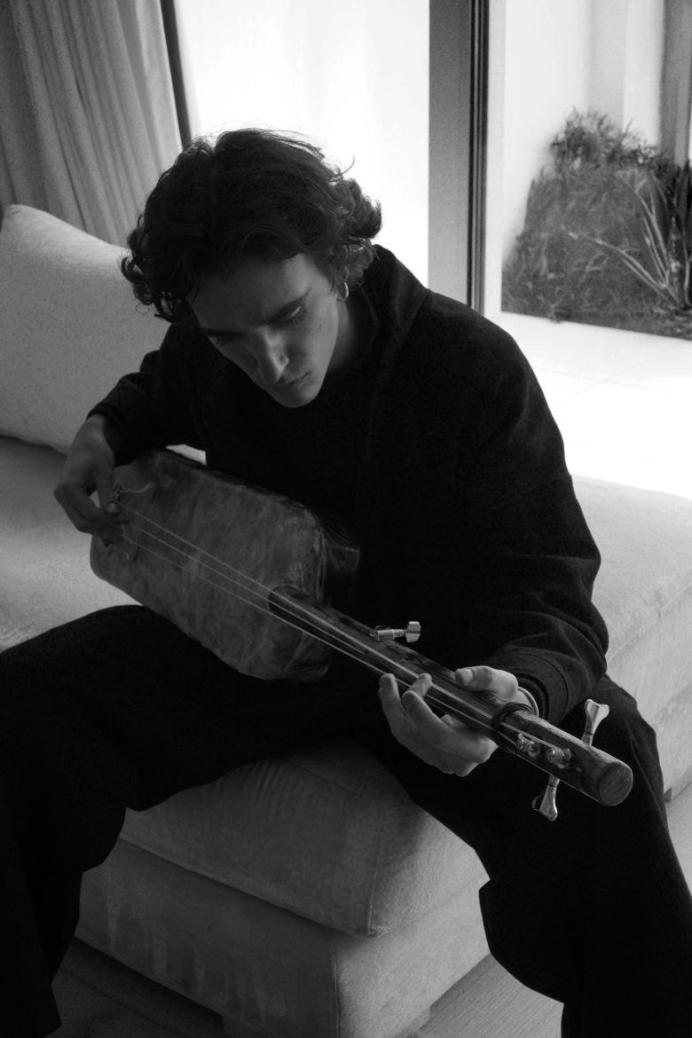 Tamino playing a traditional instrument
