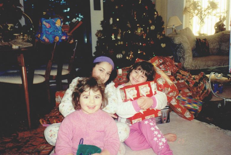 three little girls in front of a Christmas tree with presents