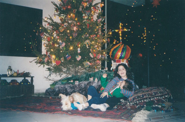 two siblings playing by the Christmas tree with a dog