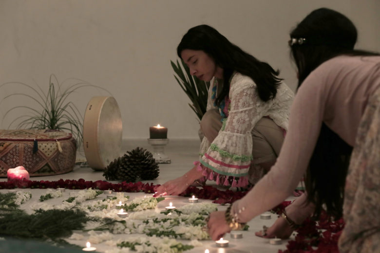 Two women lighting up candles for a meditation gathering